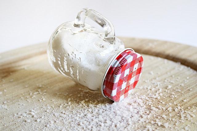 povalená slánka na stole, ze které se sype sůl