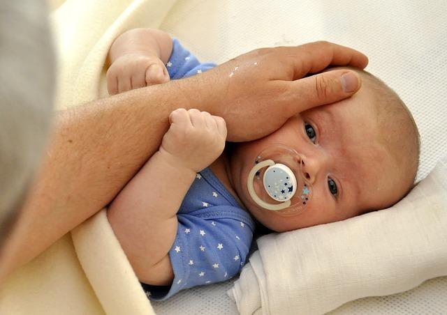 otec s láskou hladí své miminko.jpg