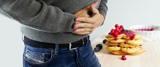muž co se drží za břicho a sladkosti.jpg