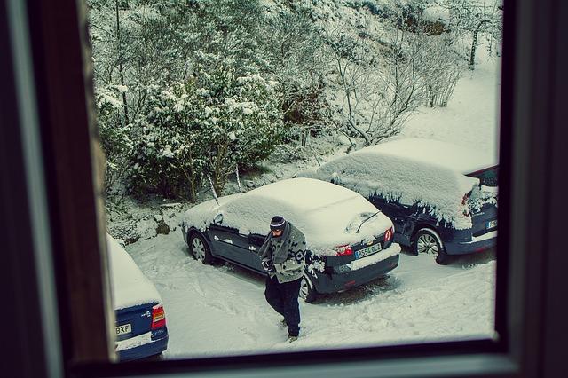 pohled z okna na zasněžená auta